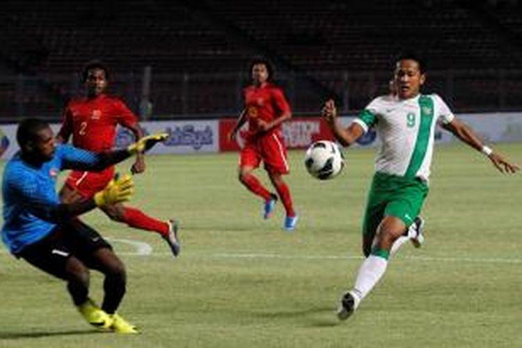 Pemain Indonesia, Yandi Sofyan Munawar (kanan) berebut bola dengan penjaga gawang Papua New Guinea, Wilbert Benjamin pada pertandingan MNC Cup 2013 di Stadion Utama Gelora Bung Karno, Jakarta, Jumat (22/11/2013). Indonesia menang 6-0