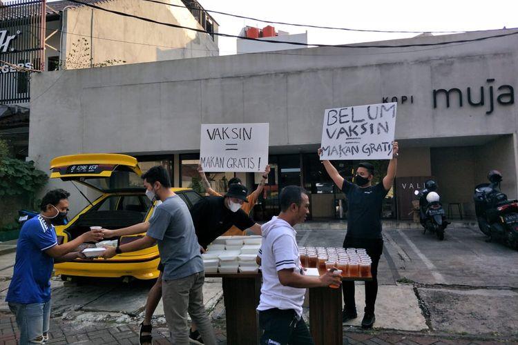 Aksi sejumlah pemuda membagikan makanan dan minuman gratis di depan kedai Kopi Muja, Kebayoran Baru, Jakarta Selatan