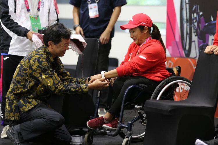 Hirokazu Satoh, Chief Representative Casio Singapore Pte, Ltd, Jakarta Representative Office berlutut memasangkan sebuah jam tangan Baby-G untuk atlet paracycling Indonesia Ni Kadek Karya Dewi, di Jakarta, Rabu (3/10/2018).