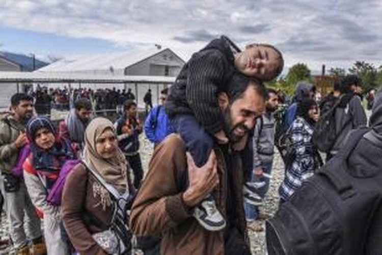 Migran dan pengungsi yang berhasil melintasi perbatasan Makedonia-Yunani, mengantre saat akan menaiki kereta di kamp registrasi dekat Gevgelija, 28 September 2015. day.