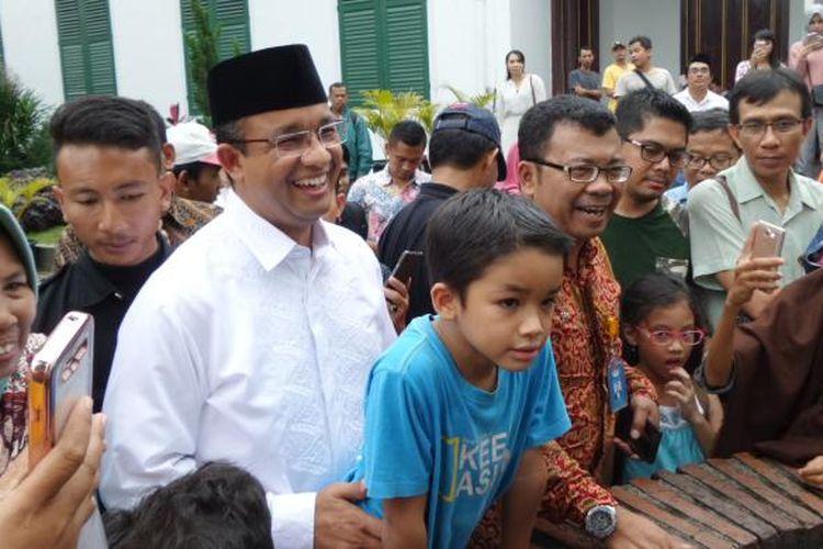 Calon gubernur DKI Jakarta Anies Baswedan bersama anak bungsunya, Ismail Hakim, melihat sumur di halaman belakang Museum Fatahillah, Jakarta Barat, Minggu (12/2/2017). Anies mengisi masa tenangnya dengan menghabiskan lebih banyak waktu bersama keluarga.