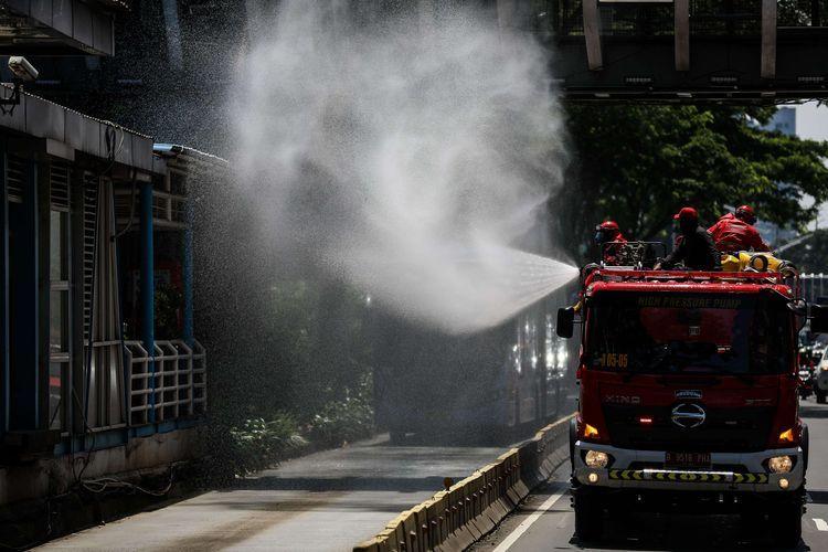 Petugas Pemadam Kebakaran (Damkar) menyemprotkan disinfektan di sepanjang jalan protokol dari monas sampai bunderan senayan di Jakarta, Selasa (31/3/2020). Penyemprotan disinfektan dalam rangka mitigasi pencegahan virus corona (COVID-19).(KOMPAS.com/GARRY LOTULUNG)