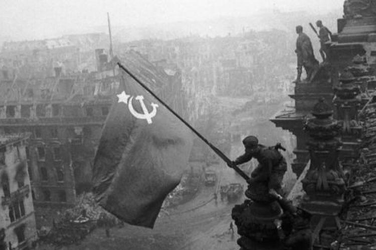Tentara Soviet mengibarkan bendera di atas gedung parlemen Jerman atau Reichstag di Berlin pada 1945.
