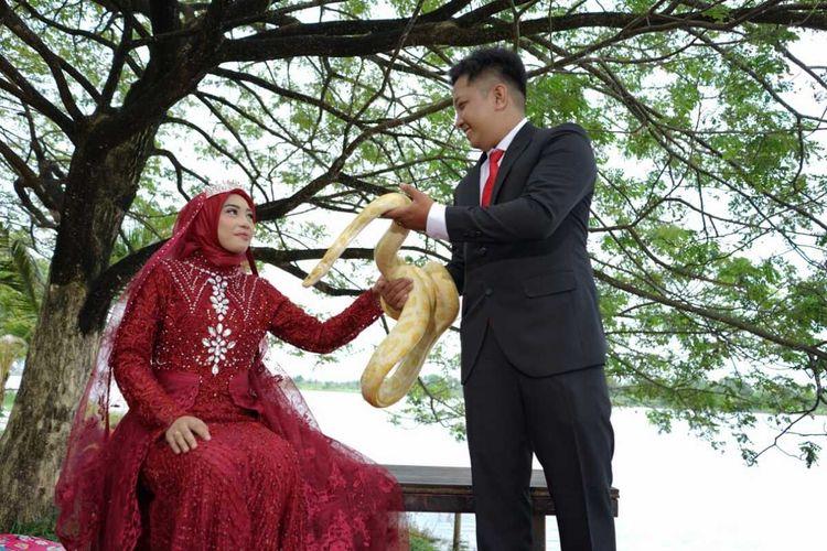 Sadam Maulana dan Desti i pasangan calon pengantin yang menggunakan ular sebagai objek foto prewedding di Palembang, Sumatera Selatan, Selasa (16/3/2021).