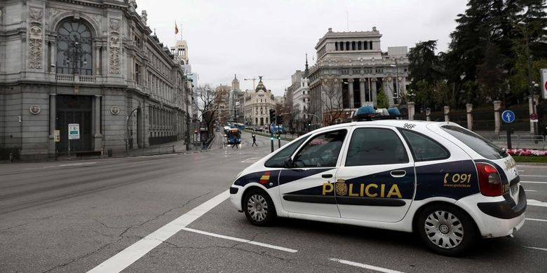 Sebuah mobil polisi berpatroli di Madrid, Spanyol, pada 20 Maret 2020, untuk memantau aktivitas warga dalam aturan lockdown yang diterapkan, terkait penyebaran virus corona yang meluas di Spanyol.