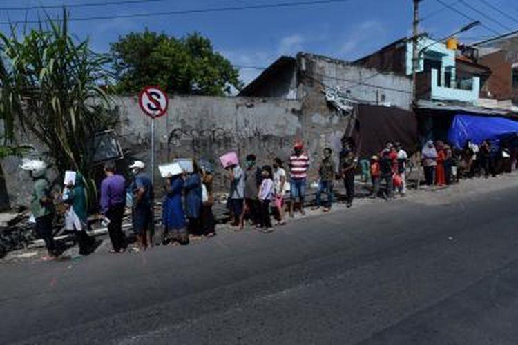 Warga mengantre mencairkan bantuan sosial tunai di Kantor Pos, di Surabaya, Jawa Timur, Kamis (14/5/2020). Antrean yang panjang akibat keterbatasan ruang tunggu akhirnya dapat diatasi setelah diberlakukan nomor antrean.