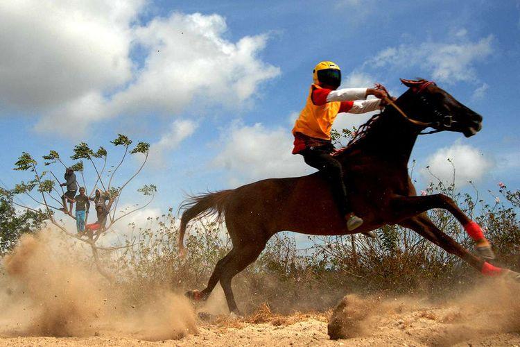 Joki beradu kecepatan saat mengikuti lomba pacuan kuda tradisional di Desa Kalimporo, Jeneponto, Sulawesi Selatan, Minggu (28/10/2018). Pacuan kuda tradisional ini terbilang unik karena jokinya bukan hanya orang dewasa tapi juga diikuti joki anak-anak yang hanya menggunakan peralatan seadanya bahkan tidak sedikit hanya menggunakan sandal.