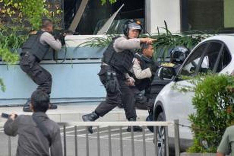 Polisi mengambil posisi dan mengarahkan senjata saat mengejar terduga pelaku di luar sebuah kafe setelah ledakan menghantam kawasan Jalan MH Thamrin, Jakarta Pusat, 14 Januari 2016. Serangkaian ledakan menewaskan sejumlah orang, terjadi baku tembak antara polisi dan beberapa orang yang diduga pelaku.