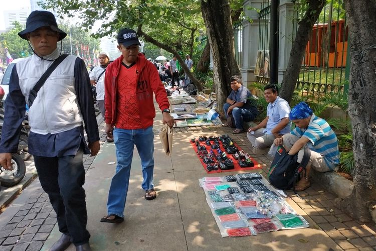 Beberapa pedagang menjajakan dagangannya di trotoar Medan Merdeka Selatan yang terletak dekat dengan Patung Kuda yang merupakan titik masuk massa ke area aksi MK (27/6)