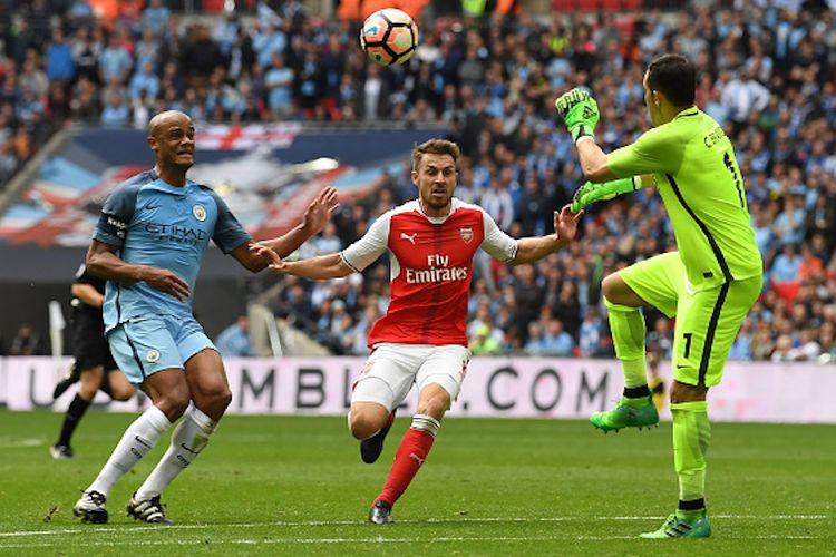 Vincent Kompany, Aaron Ramsey, dan Claudio Bravo terlibat dalam perebutan bola pada pertandingan semifinal Piala FA antara Manchester City dan Arsenal di Stadion Wembley, Minggu (23/4/2017).