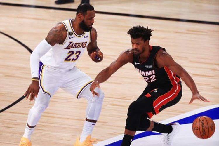 LeBron James (kiri) mengawal Jimmy Butler (kanan) pada Gim 6 Final NBA 2020 yang mempertemukan LA Lakers vs Miami Heat di AdventHealth Arena, Orlando, Amerika Serikat, Senin (12/10/2020) pagi WIB.
