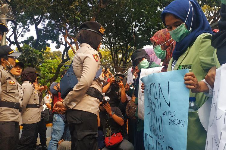 Polwan dan mahasiswi berhadap-hadapan dalam aksi unjuk rasa BEM SI di sekitar Patung Kuda, Jalan Medan Merdeka Barat Jakarta Pusat, Kamis (17/10/2019).