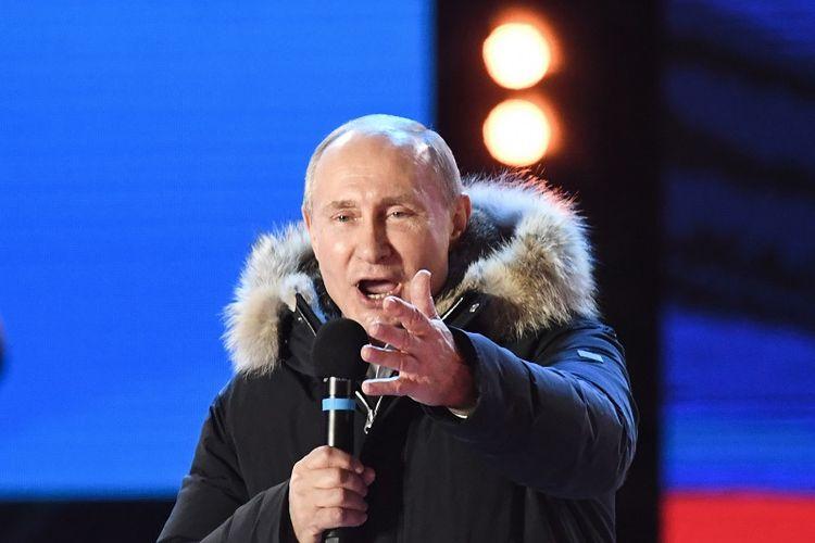 Presiden Vladimir Putin berpidato kepada para pendukungnya dalam kampanye dan konser memperingatik ulang tahun keempat aneksasi Crimea di Lapangan Manezhnaya, Moskwa pada Minggu (18/3/2018).