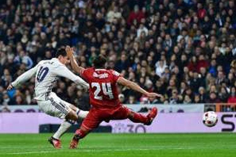James Rodriguez menembak bola seusai melewati hadangan bek Sevilla, Gabriel Mercado, pada pertandingan Copa del Rey di Santiago Bernabeu, Rabu (4/1/2017).