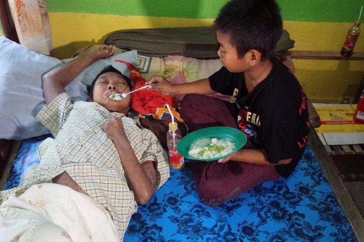 Muhammad Gunadiono (11), seorang murid kelas 5 SDN Gedongombo 2, Kecamatan Ploso, Kabupaten Jombang, Jawa Timur, saat menyuapi ibunya yang hanya bisa terbaring di atas ranjang karena stroke.
