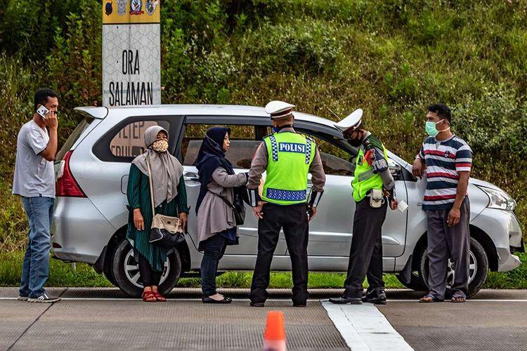 Polisi menginterogasi sejumlah penumpang yang diduga menumpang mobil bernomor polisi palsu saat penyekatan pemudik di Gerbang Tol Kalikangkung, Semarang, Jawa Tengah, Selasa (26/5/2020). Satlantas Polrestabes Semarang mencatat sejak pukul 07.00-17.00 WIB sebanyak 276 kendaraan roda empat maupun bus yang mengangkut pemudik menuju Jakarta melalui gerbang tol tersebut diperintahkan untuk berputar balik karena tidak dilengkapi surat izin keluar-masuk (SIKM).