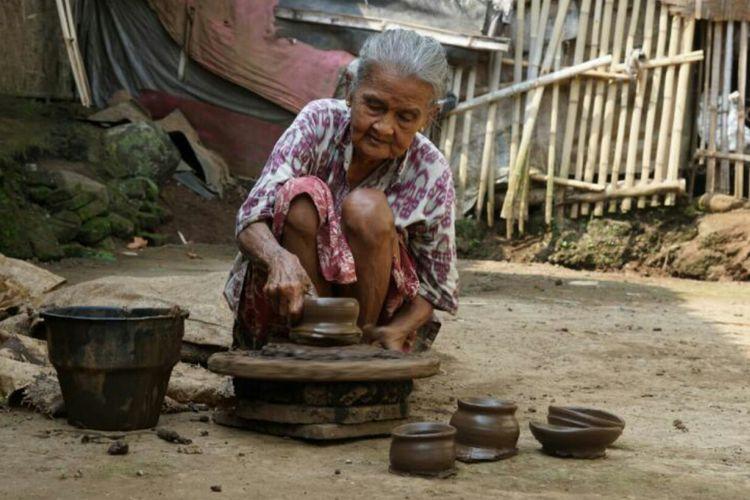 Mbah Boni sedang membuat mainan dari tanah liat. Aktivitasnya ini ia lakukan sejak jaman Jepang.