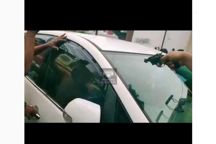 Sejumlah polisi ketika menangani seorang remaja berinisial JS (18) yang mengacungkan sepucuk senjata mainan kepada seorang pemotor di Jalan Kedoya Raya, Kebon Jeruk, Jakarta Barat, Minggu (14/2/2021) sore.