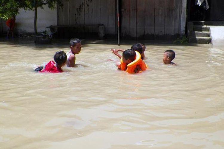 Anak-anak di Desa Dukun Anyar di Kecamatan Dukun, Gresik, sedang asyik bermain air banjir yang merendam desanya, Minggu (27/11/2016).