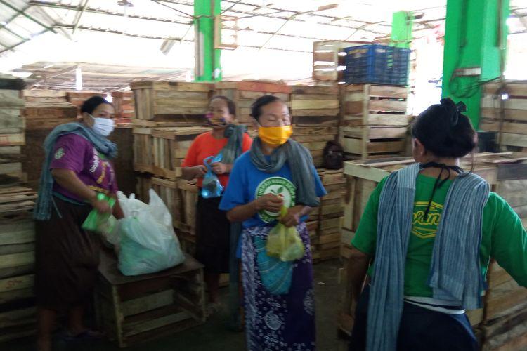 Para buruh gendong perempuan di pasar giwangan sata menerima nasi bungkus