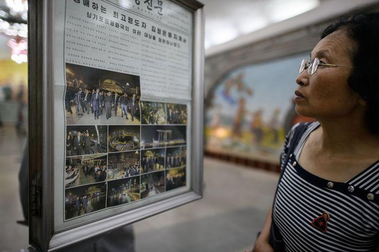 Seorang warga Korea Utaara membaca edisi terbaru harian Rodong Sinmun yang menampilkan sedert foto Kim Jong Un sedang berjalan-jalan di Singapura, Senin (11/6/2018).