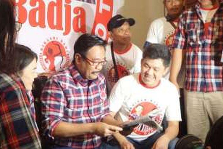 Bakal cawagub DKI Djarot Saiful Hidayat mencoba kacamata baca yang dibagikan relawan Barisan Relawan Basuki Djarot di Cipinang,Minggu (23/10/2016).
