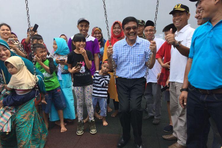 Gubernur DKI Jakarta Djarot Saiful Hidayat bermain ayunan saat berkunjung ke RPTRA/RTH Kalijodo, Jakarta Utara, Jumat (30/6/2017) pagi.