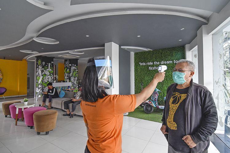 Seorang petugas mengecek suhu tubuh pengunjung yang akan menginap di Fizz Hotel di Mataram, Lombok, NTB, Selasa (21/4/2020). Di tengah pandemi virus corona, Fizz Hotel bekerja sama dengan rumah sakit Unram menyediakan paket isolasi mandiri selama 14 hari  seharga Rp7 juta dengan layanan lengkap seperti layanan medis, rapid tes sebanyak dua kali dan layanan makanan yang bergizi.