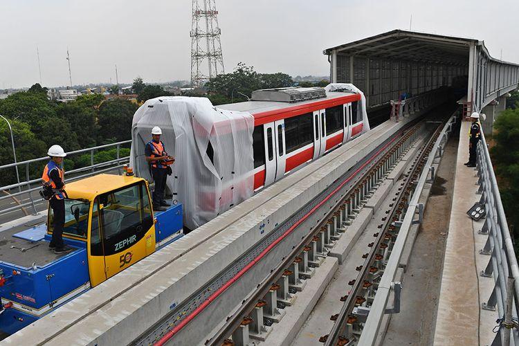 Sejumlah petugas mengoperasikan alat pendorong gerbong kereta light rail train atau lintas rel terpadu (LRT) yang telah diangkat ke atas rel di Stasiun Harjamukti, Cimanggis, Kota Depok, Jawa Barat, Rabu (4/12/2019). Saat ini sebanyak dua dari total 31 rangkaian kereta (train set) LRT buatan PT INKA telah diangkat di atas rel Stasiun Harjamukti dan ditargetkan selesai seluruhnya pada 2020.