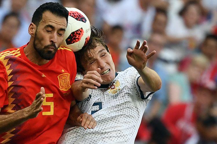 Pemain Spanyol Sergio Busquets (kiri) beradu sundulan dengan pemain Rusia Mario Fernandes pada laga 16 besar Piala Dunia 2018 di Stadion Luzhniki, Minggu (1/7/2018). Timnas Rusia lolos ke babak perempat final setelah menyingkirkan Spanyol lewat drama adu penalti dengan skor 4-3.