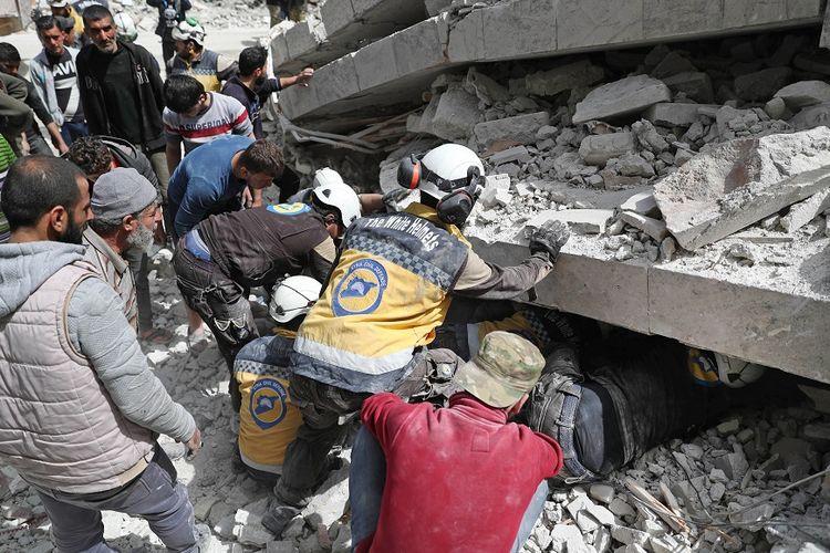 Petugas dari Pertahanan Sipil Suriah (SCD) atau Helm Putih, memeriksa reruntuhan bangunan yang hancur akibat serangan udara yang dilancarkan pasukan rezim Suriah dan sekutunya, Rusia, ke kawasan Idlib, 24 April 2019.