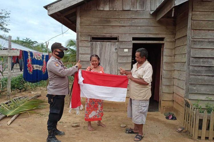Bhabinkamtibmas Bripka JF Hutabarat menyerahkan bendera merah putih secara gratis kepada warga Suku Talang Mamak di Desa Talang Tujuh Buah Tangga, Kecamatan Rakit Kulim, Kabupaten Inhu, Riau, Jumat (7/8/2020).