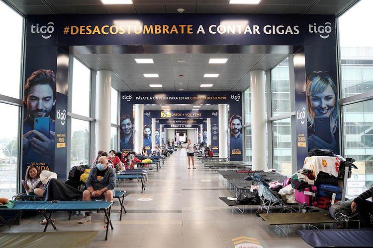 Warga yang menempati tempat tidur sementara beristirahat di Bandara Internasional El Dorado beberapa jam setelah pemerintah Kolombia memerintahkan 19 hari isolasi kawasan sebagai upaya menghambat penularan virus corona (COVID-19), di Bogota, Kolumbia, Selasa (24/3/2020).
