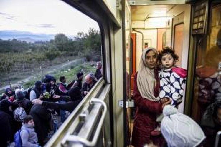Seorang ibu menggendong anaknya saat naik kereta yang menuju ke Serbia bersama para migran dan pencari suaka lainnya, setelah melintasi perbatasan Makedonia-Yunani dekat Gevgelija, 28 September 2015.