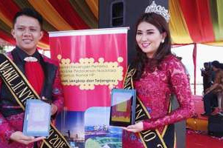 Nona Manado memperagakan sebuah tablet dengan logo Dompetku dari Indosat Ooredoo dalam peresmian Dompetku Nusantara di Balai Pelelangan Ikan, Bitung, Sulawesi Utara, Rabu (3/2/2016).