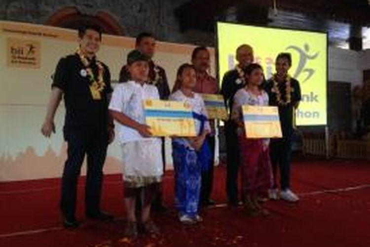 Para petinggi BII Maybank berpose dengan siswa sekolah dasar di Gianyar, pada acara CSR jelang BII Maybank Bali Marathon, Sabtu (13/9/2014).