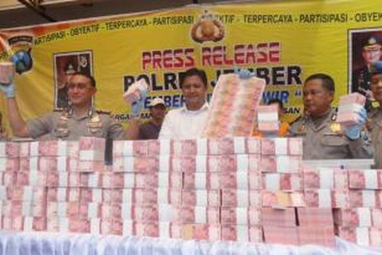 Kapolres Jember, Jawa Timur, AKBP Sabilul Alif, bersama Kasatreskrim Polres Jember, AKP Rony Setyadi, memamerkan uang palsu sebanyak Rp 12,2 Milyar, Senin (26/1/2015).