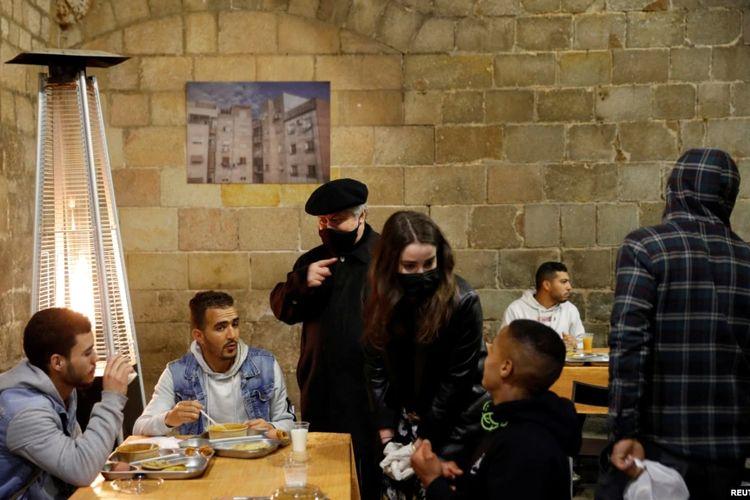 Pastor Peio Sanchez berbincang dengan para hadirin yang ikut berbuka puasa Ramadan di gereja Santa Anna di tengah pandemi Covid-19, di Barcelona, ??Spanyol, 28 April 2021.