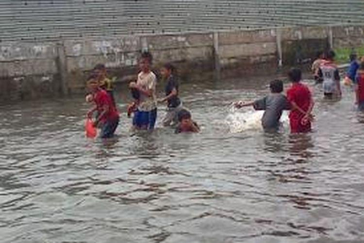 Anak-Anak memanfaatkan banjir di Jalan Masjid At-Taqwa, Kembangan, Jakarta Barat sebagai wanaha berenang gratis, Selasa (10/2/2015).