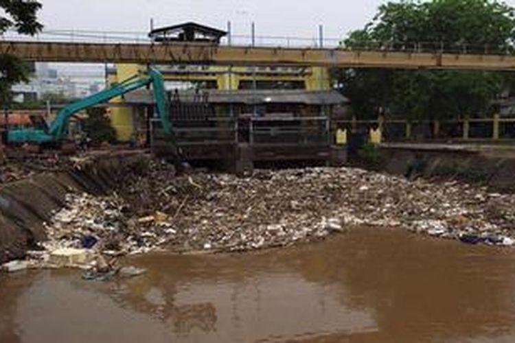 Pekerja menunggu truk untuk mengangkut sampah yang menumpuk di Pintu Air Manggarai, Jakarta Selatan, Senin (22/10/2012). Sampah tersebut menumpuk karena hujan mulai turun dan terbawa oleh aliran Sungai Ciliwung.