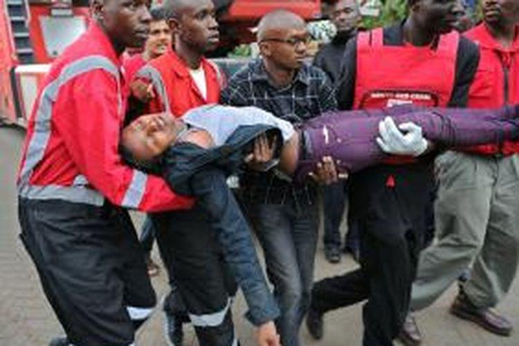Anggota palang merah Kenya membopong seorang perempuan yang baru saja dibebaskan kelompok bersenjata yang menyerbu sebuah pusat perbelanjaan di ibu kota Nairobi.
