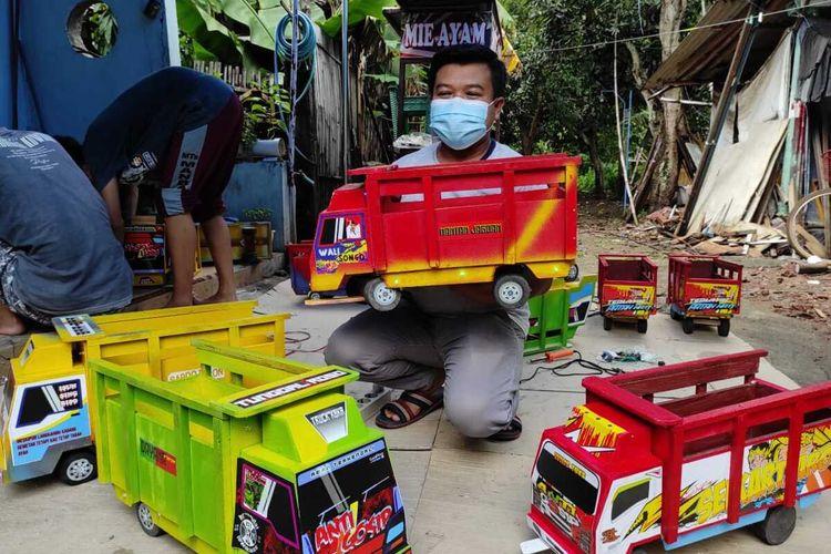 MINIATUR--Arif Budianto, warga Jalan Wilis, Kelurahan Nologaten, Kecamatan Ponorogo, Kabupaten Ponorogo menunjukkan karya-karyanya berupa miniatur truk oleng yang lagi diminati banyak orang. Dalam satu bulan pria asal bumi reyog itu bisa meraup omzet hingga Rp 20 juta.
