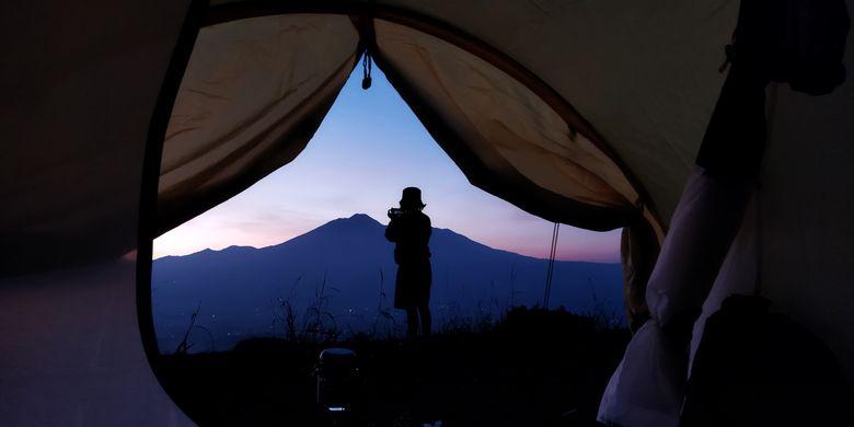 Seorang wisatawan tengah menikmati pemandangan Gunung Gede Pangrango detik-detik menjelang momen golden sunrise yang dilihat dari Desa Pasirjaya, Kecamatan Cigombong, Kabupaten Bogor pada Kamis (27/5/2021).