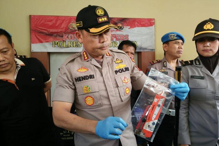 Kepala Polresta Bogor Kota Komisaris Besar Hendri Fiuser saat menunjukkan barang bukti cutter yang digunakan pelaku untuk membunuh seorang pengemudi taksi online, di Mapolres Bogor Kota, Senin (4/11/2019).