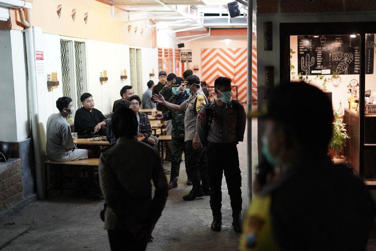 Polisi membubarkan kerumunan orang di sebuah kafe.