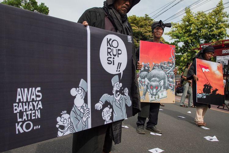 Warga membawa poster anti korupsi pada Hari Peringatan Hari Anti Korupsi Sedunia di Solo, Jawa Tengah, Minggu (9/12/2018). Selain dalam rangka memperingati Hari Anti Korupsi aksi tersebut juga untuk mendorong Pemerintah dan KPK memberikan hukuman seberat-beratnya kepada pelaku korupsi. ANTARA FOTO/Mohammad Ayudha/foc.
