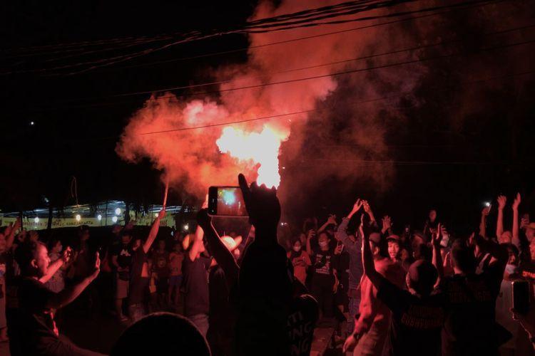 Sejumlah pendukung Persija merayakan kemenangan Persija Jakarta dengan bernyanyi sambil menyalakan flare seusai nonton bareng di pinggir Jalan Raya Pasar Minggu, Kalibata, Jakarta Selatan pada Minggu (25/4/2021) malam.