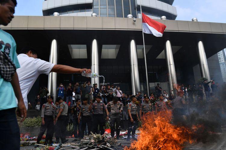 Polisi berjaga saat berlangsung unjuk rasa berujung ricuh yang dilakukan sejumlah orang tergabung dalam Aliansi Mahasiswa dan Pemuda Relawan Cinta NKRI di kantor KPK, Jakarta, Jumat (13/9/2019).