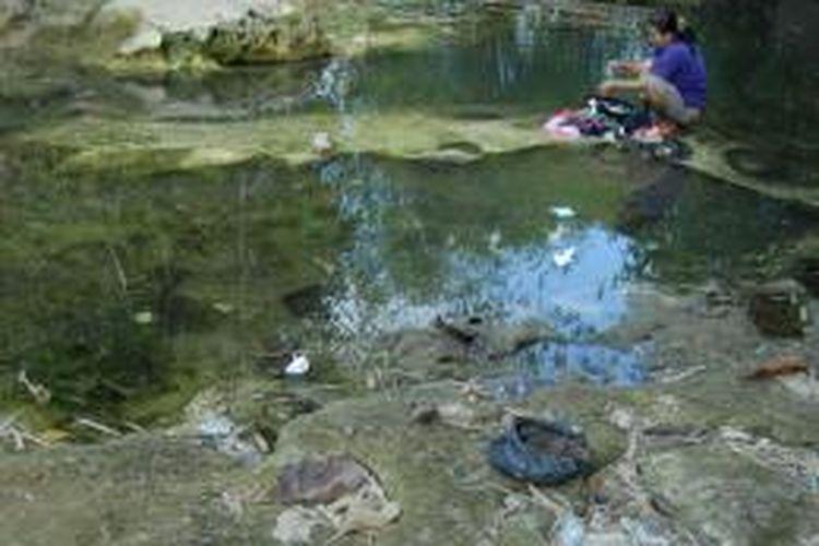 Warga Desa Blumbungan, Kecamatan Larangan, terpaksa menggunakan air sungai yang sudah berlumut di sungai yang berhenti mengalir, untuk mencuci dan mandi.