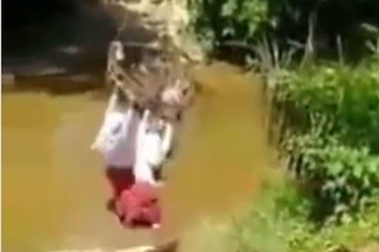 Viral di media sosial tiga anak sekolah dasar (SD) menyeberangi sungai dengan cara bergelantungan.
